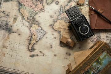 top view of vintage camera, notepad with fountain pen, stamp and painting on map background
