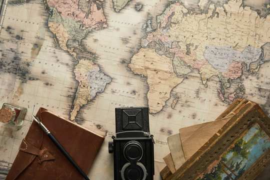 top view of vintage camera, notepad with fountain pen and painting on map background