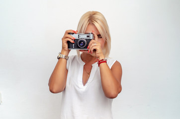 Blonde woman takes pictures using a film camera.