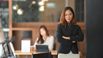 Confidently  asian businesswoman standing on front of office workplace.