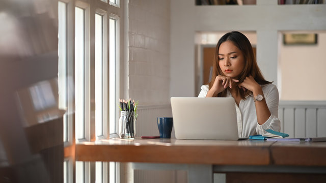 Asian woman working on home office table with thinking moment on laptop.