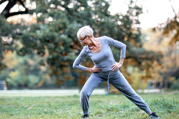 Mature woman exercise in the bark and smile Wall mural