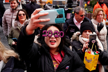 A woman takes photos as workers set up the numerals 2 and 0 for News Year's Eve in Times Square in the Manhattan borough of New York City