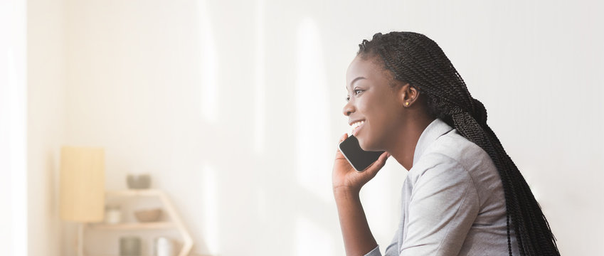 Smiling African American Businesswoman Talking On Cellphone In Office