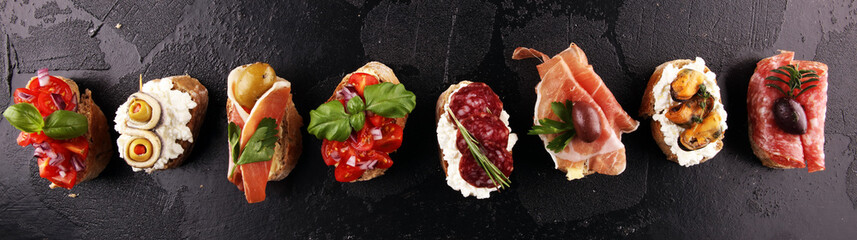 Photo sur Aluminium Snack Appetizers table with italian antipasti snacks and wine in glasses. Brushetta or authentic traditional spanish tapas set, cheese variety