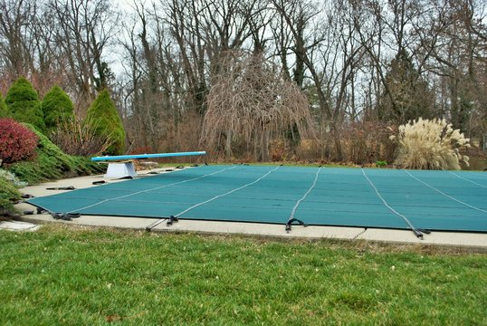 backyard swimming pool with diving board and pool slide tarped up and closed down for winter