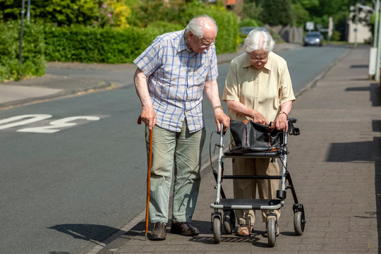 Elderly Couple with Walking Frame and Stick on the Sidewalk