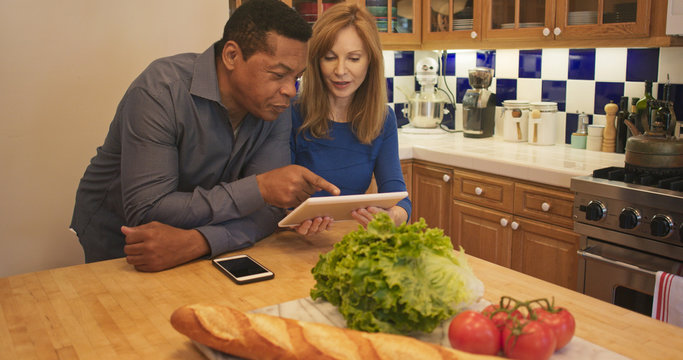 Mature couple standing in kitchen looking at recipe on tablet computer