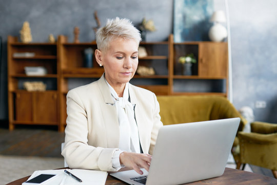Beautiful trendy looking 50 year old businesswoman in stylish suit keyboarding on portable computer, sitting at office desk with smart phone and copybook. Technology and occupation concept