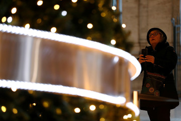 A woman takes a picture of a decorated Christmas tree at Galleria Colonna in Rome