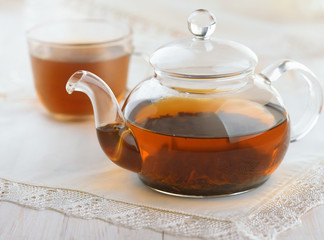 Glass teapot and cup full of fresh black tea