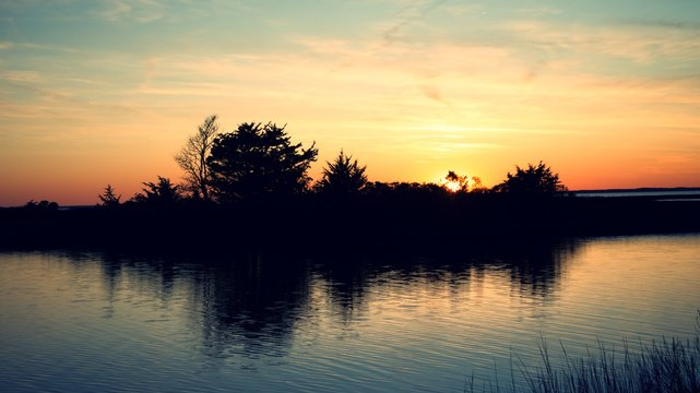 Sunset over Assateague Island over marshes, salt water bay with silhouette