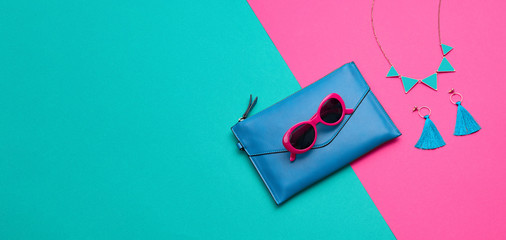 Fashion party girl layout Flat lay. Minimal. Woman Essentials accessories. Trendy Clutch, sunglasses, earrings. Coloful pink green Set. Creative pop art concept, vibrant fashionable color. Banner