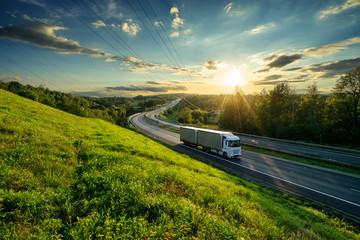 Fotobehang - White truck driving on the asphalt highway in landscape at sunset