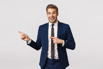 Surprised, cheerful handsome blond guy in classic suit, pointing left and smiling amused, hearing wonderful event nearby, standing white background joyful, promote product Wall mural