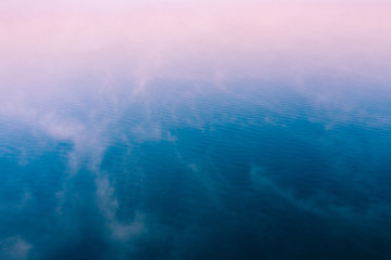 Pink fog over blue water surface, aerial view. Tranquil natural background