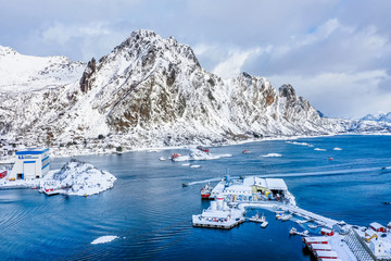 Svolvaer - Norwegian town on Lofoten Islands over polar circle. Winter snowy scene of fishing boat sailing back to home port with catch at picturesque white mountains background.