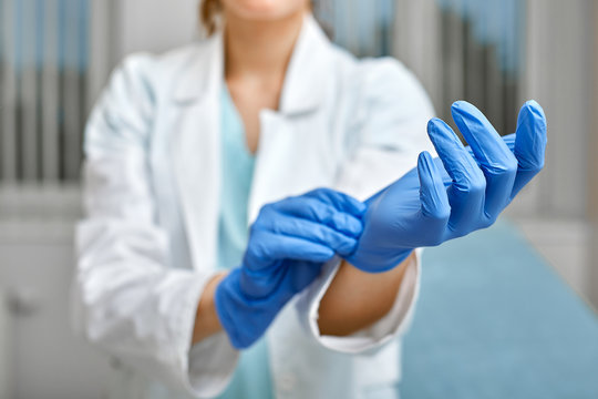 Close up of a female doctor putting a blue latex gloves on a clinic background.