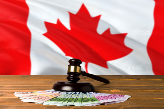 Canada bribing concept. Law theme, mallet of the judge on wooden desk with national flag background.