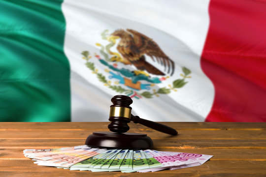 Mexico bribing concept. Law theme, mallet of the judge on wooden desk with national flag background.