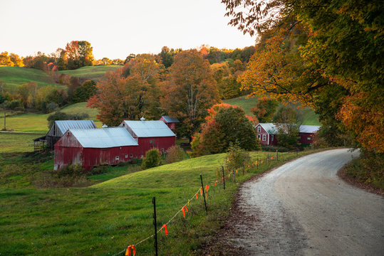Traditional American red barn along a gravel road in a rolling autumnal landscape at sunset. Woodstock, VT, USA.
