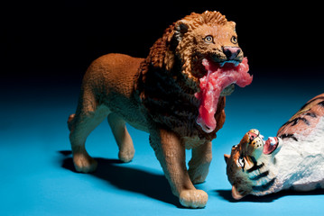 Conceptual photo of toy lion carrying raw meat with tiger