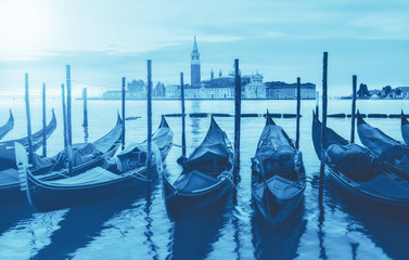 Trendy monochrome image toned in classic blue, color of the year 2020. Gondolas moored by Saint Mark square with San Giorgio di Maggiore church in Venice, Italy.