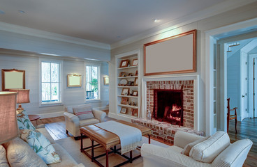Beautiful living room in expensive home with burning fireplace and large blank picture over the mantle