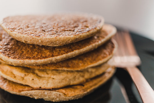 close-up of vegan banana pancakes stack on black plate with copper fork