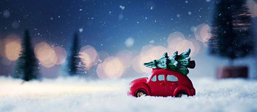 Driving home for christmas - red car with christmas tree in a romantic winter scene...