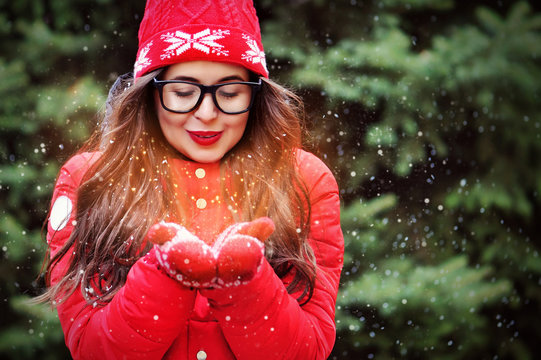 Woman wearing red jacket and hatl blowing snow off