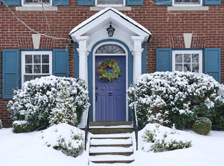 Front door of snow covered house with Christmas wreath