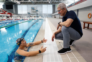 Apple's CEO Tim Cook speaks with Singapore Paralympian Theresa Goh about the Apple watch she uses for training at the OCBC Aquatic Centre, Singapore Sports Hub