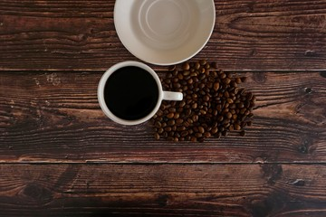 cup of coffee and beans on wooden table