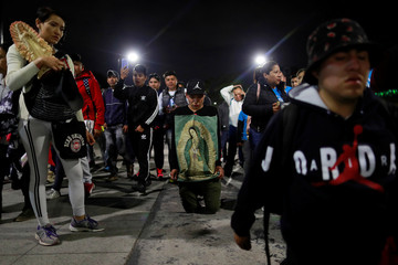 A man walks on his knees with an image of Virgin of Guadalupe towards the Basilica of Guadalupe during the annual pilgrimage in honor of the Virgin of Guadalupe, patron saint of Mexican Catholics, in Mexico City