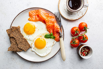 Top view of healthy breakfast with fried eggs and smoked salmon in a plate