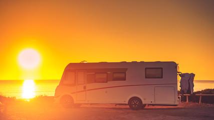 Camper car on beach at sunset