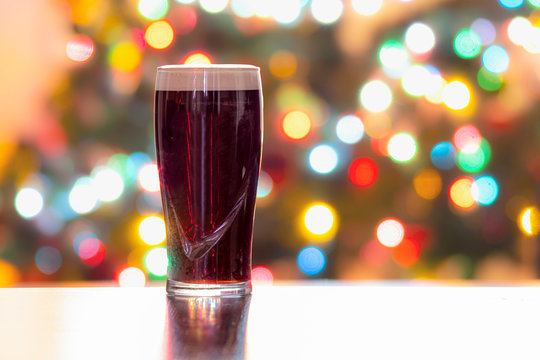 A Stouts Dark Beer with Christmas lights on the background. Guinness dark Irish dry stout. Horizontal View