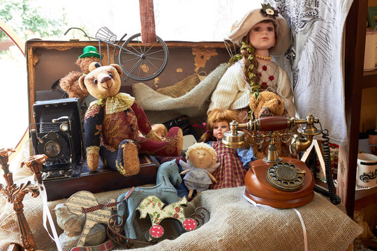 Suitcase with toys and dolls (Teddy bear) and a vintage telephone. Vintage style