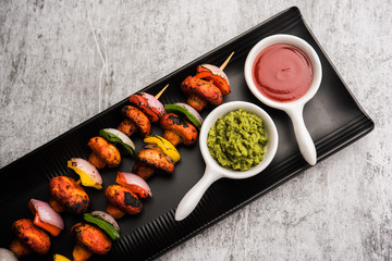 Barbecue or tandoori Mushroom Tikka, served in a plate with green chutney and ketchup. selective focus