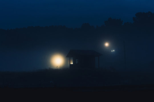 cabin in the night fog. lonely shack at night. scary creepy house at night in a swamp.