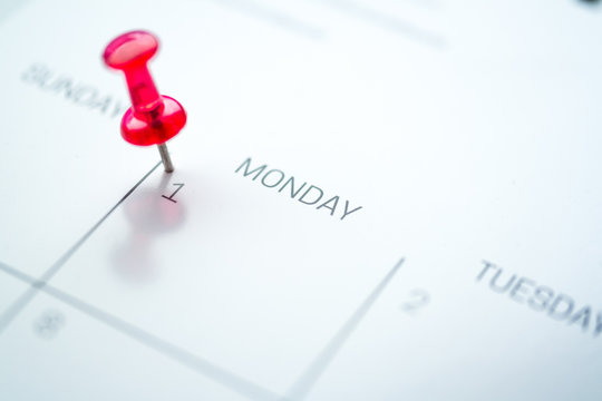 Red push pin on calendar 1st day of the month