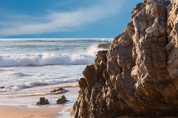 fragment of a sandy beach with a moving sea wave and a picturesque rock in the foreground near the Portuguese city of Sintra