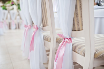Beautiful wedding set decoration in the restaurant. Pink ribbons on chairs.