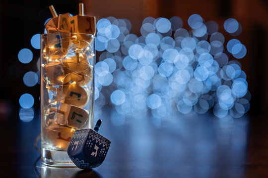 jewish holiday Chanukah/Hanukkah with wooden dreidels / sovivon (spinning top) in the glass over glitter shiny background. Traditional invitation card design