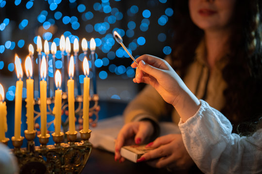 jewish holiday Chanukah/Hanukkah family selebration. Jewish festival of lights. Children lighting candles on traditional menorah over glitter shiny background