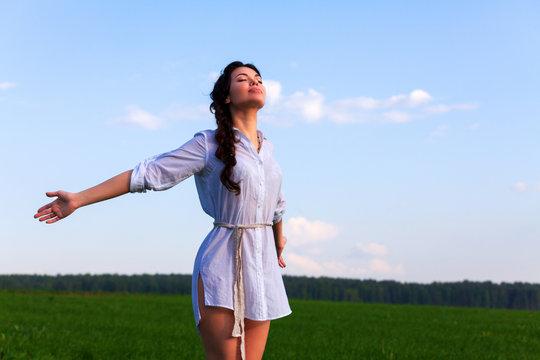 Pretty woman enjoys clear air in the summer field