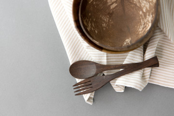 recycling, tableware and eco friendly concept - close up of coconut bowl with brown wooden spoon and fork on table