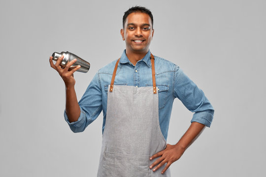 alcohol drinks, people and profession concept - indian barman in apron with cocktail shaker over grey background