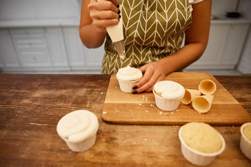 Cropped view of confectioner pouring cream on cupcakes beside waffle cones on cutting board